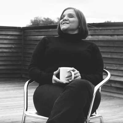 Leonie Watson sitting in a chair holding a cup of tea while smiling.
